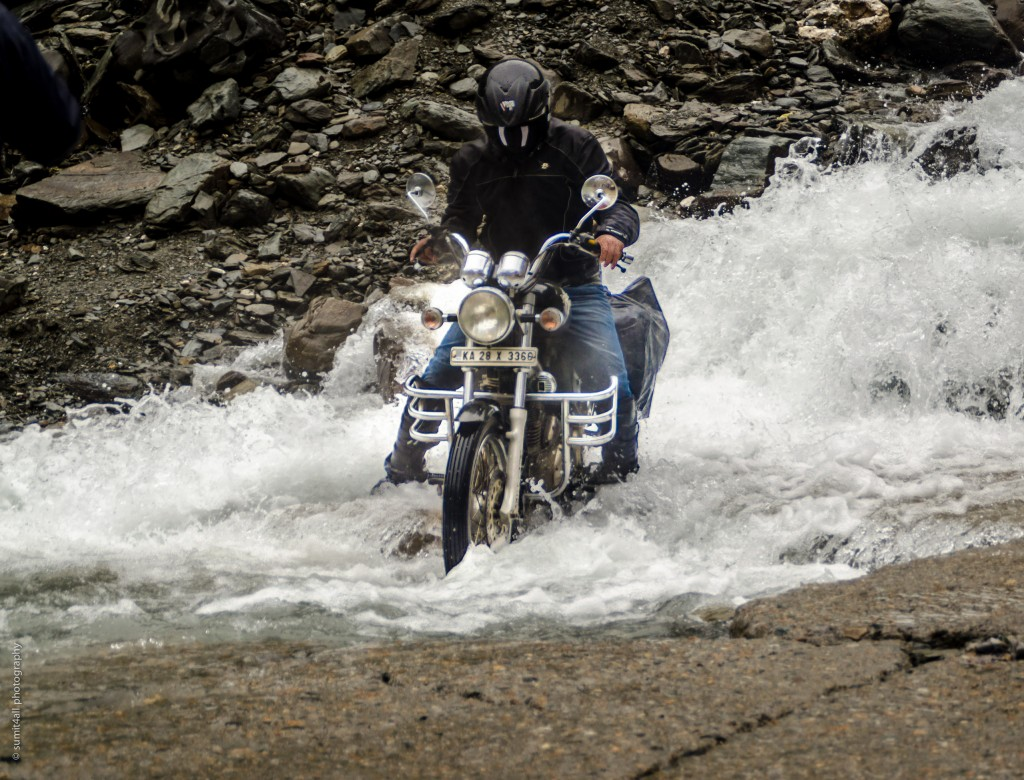 A biker navigates through a water crossing near Sarchu