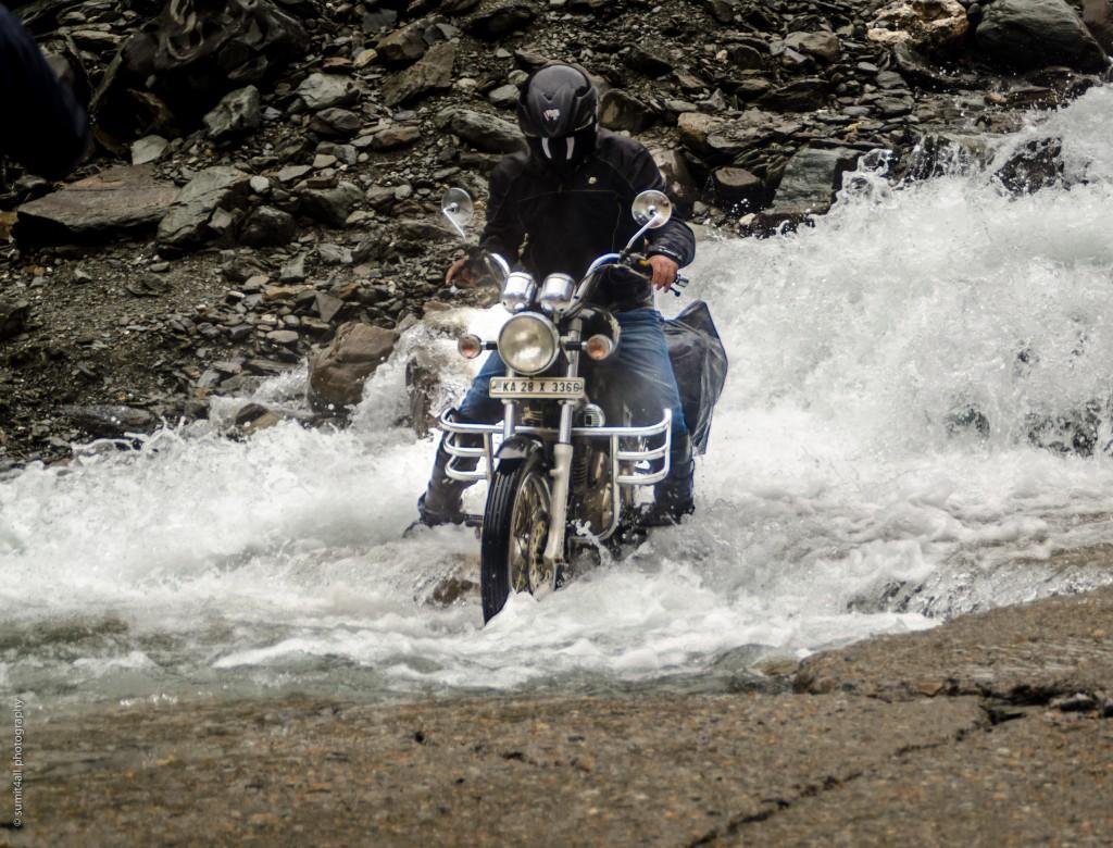 A biker navigates through a water crossing near Sarchu
