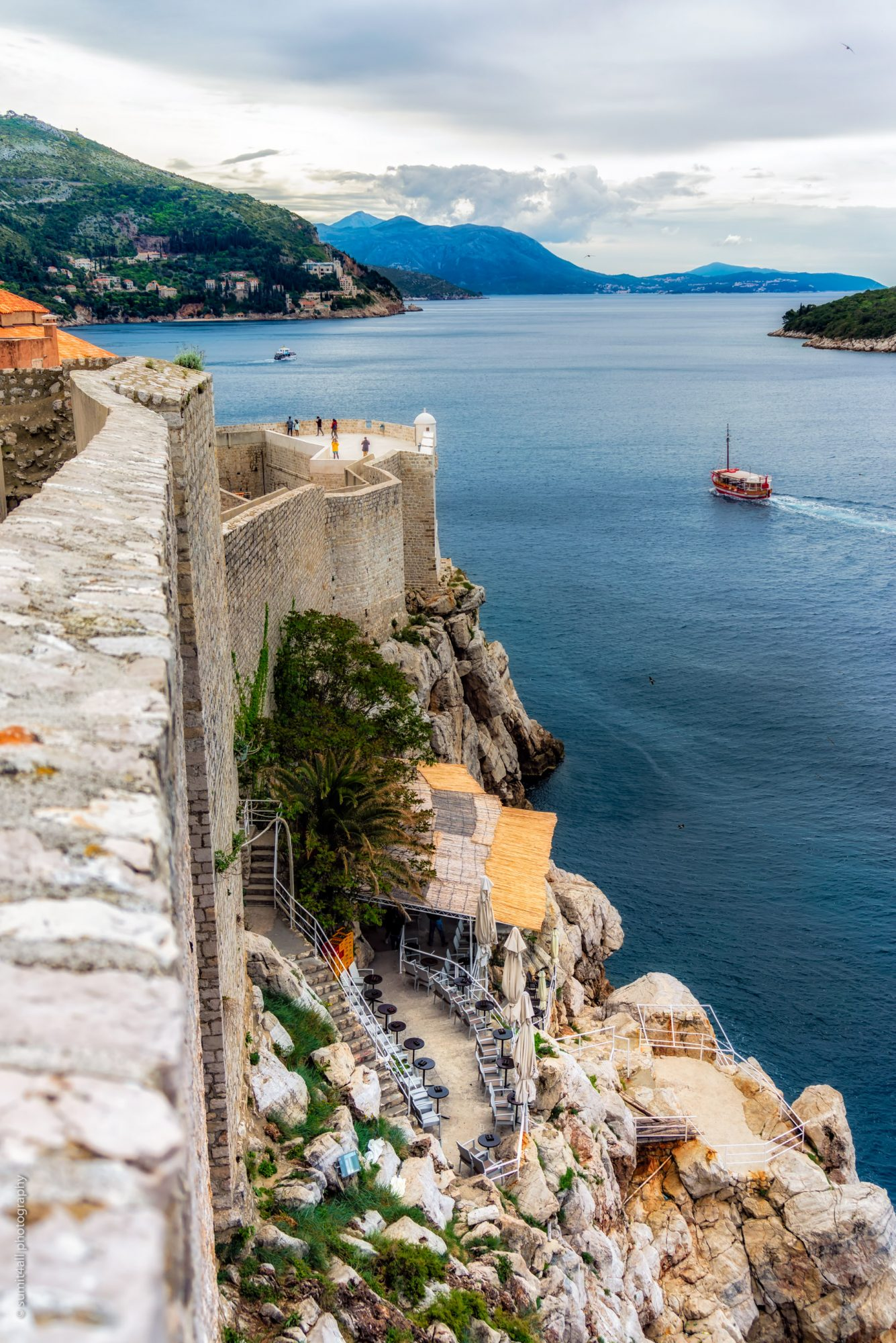 Boats cruising in the Adriatic Sea alongside the City Walls of Dubrovnik