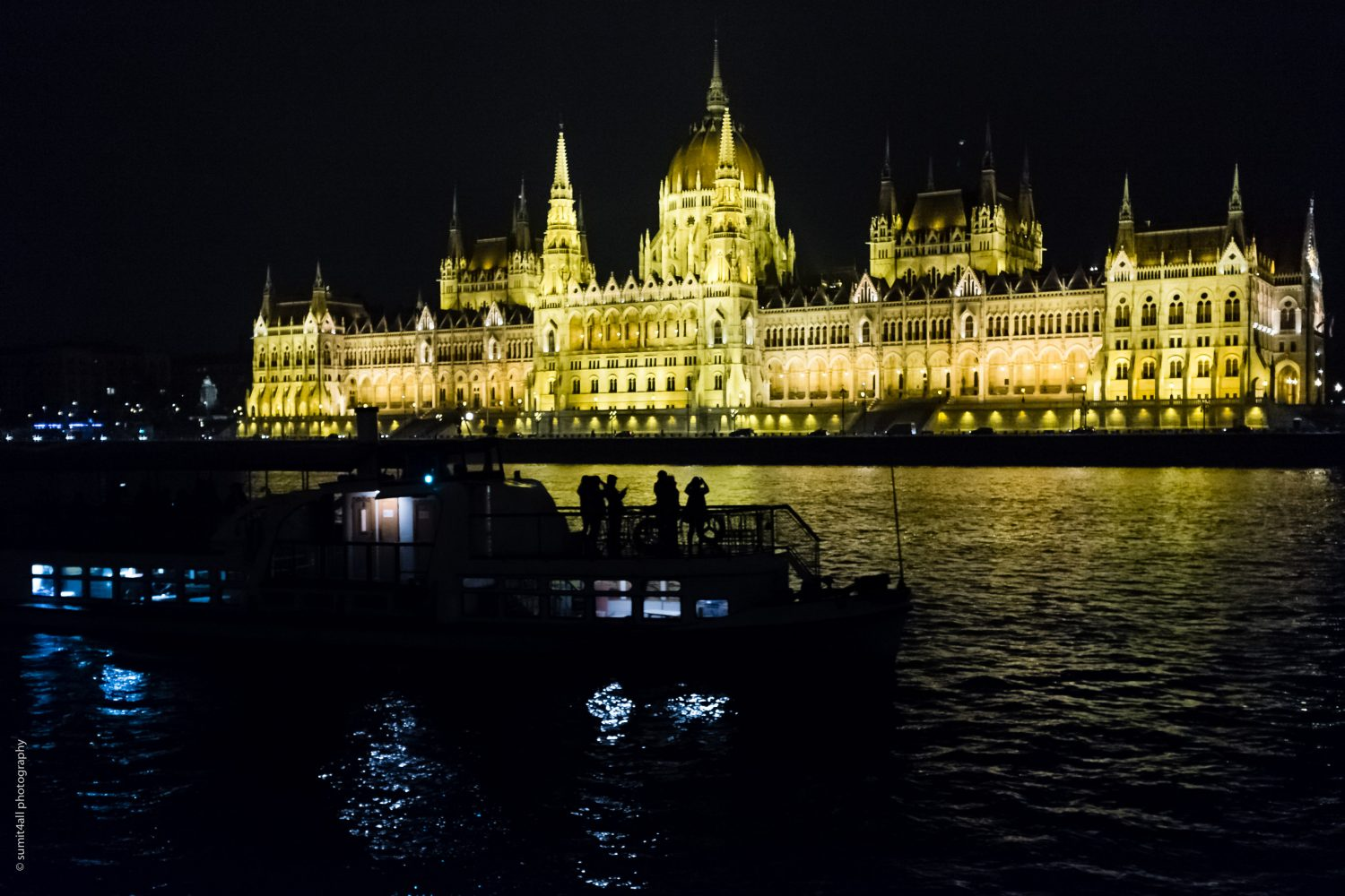 The Hungarian Parliament building and people taking photos from a boat.