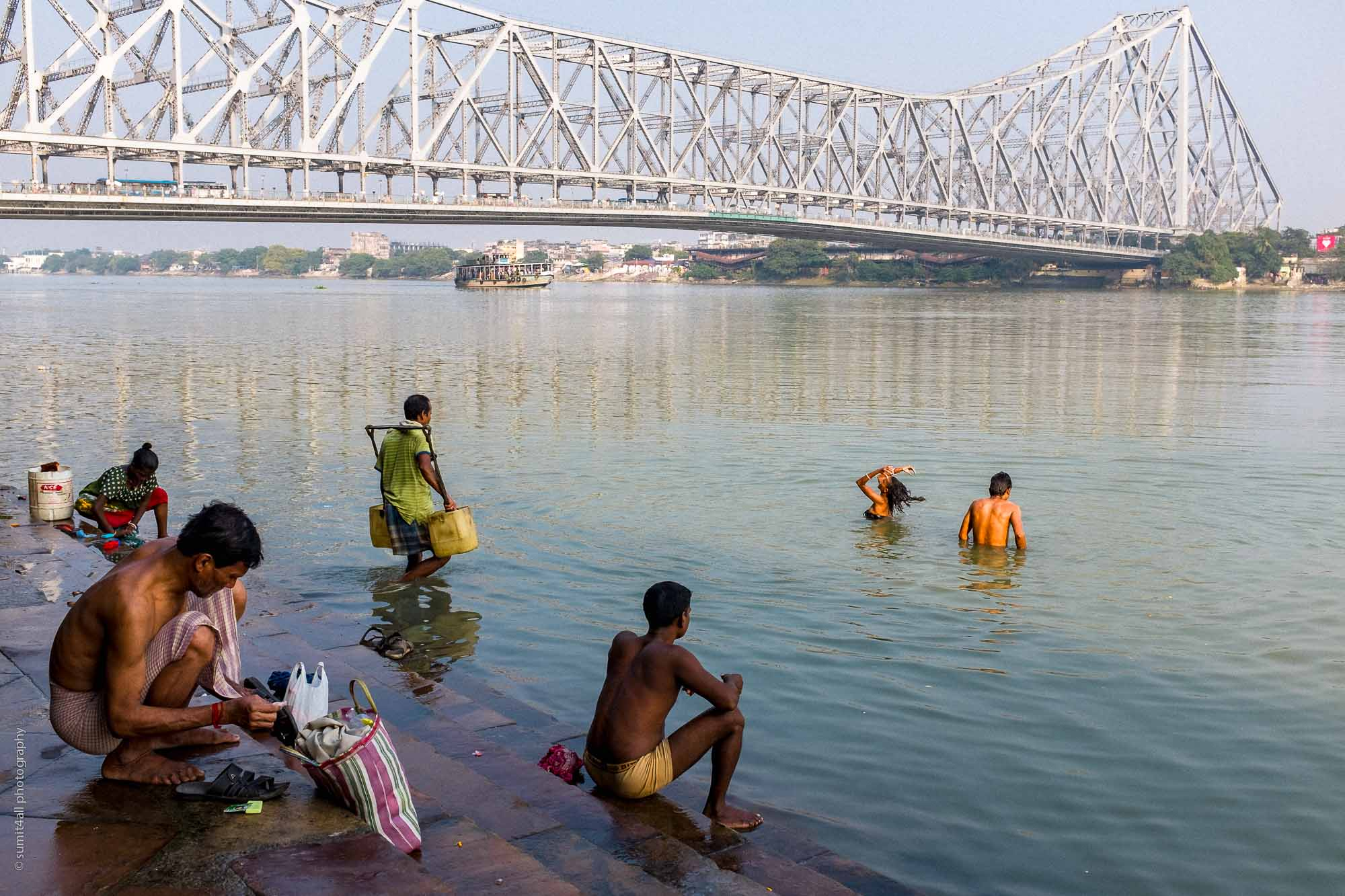 People bathing near the Howrah Bridge in Kolkata
