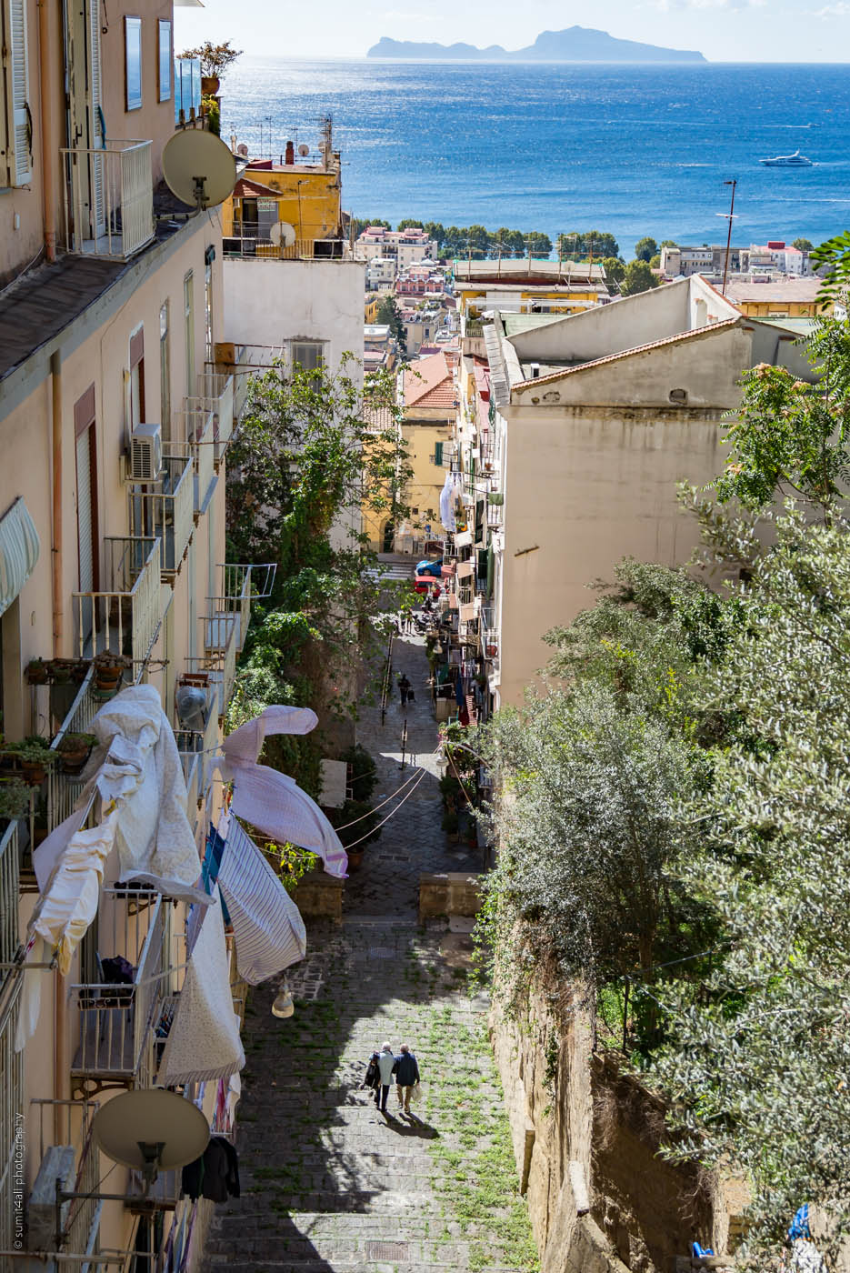 A hilly street sloping down in Naples and the Isle of Capri in the Background