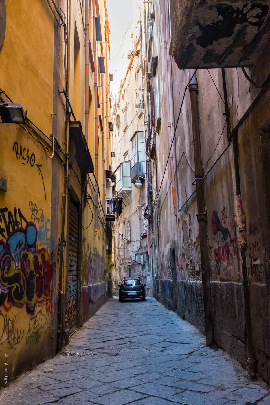 A car passes through a narrow road in Naples, Italy