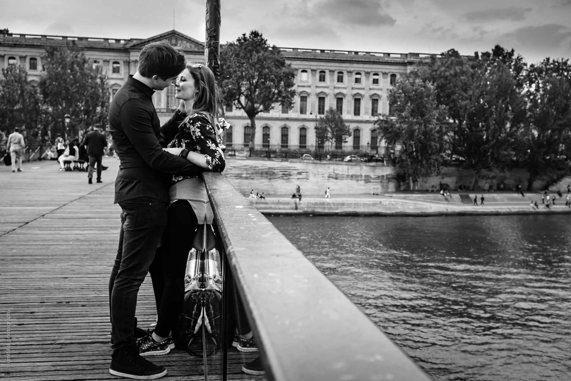 A couple kiss over a bridge on the Seine River in Paris
